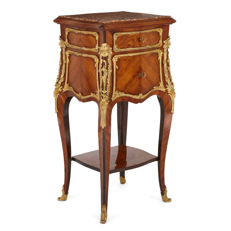 Each unit in this pair of bombe form bedside cabinets is surmounted by a veined marble top. The body of each cabinet contains a shallow upper drawer above a drop front marble-lined shelf. The cabinets stand on cabriole legs, which are connected by a