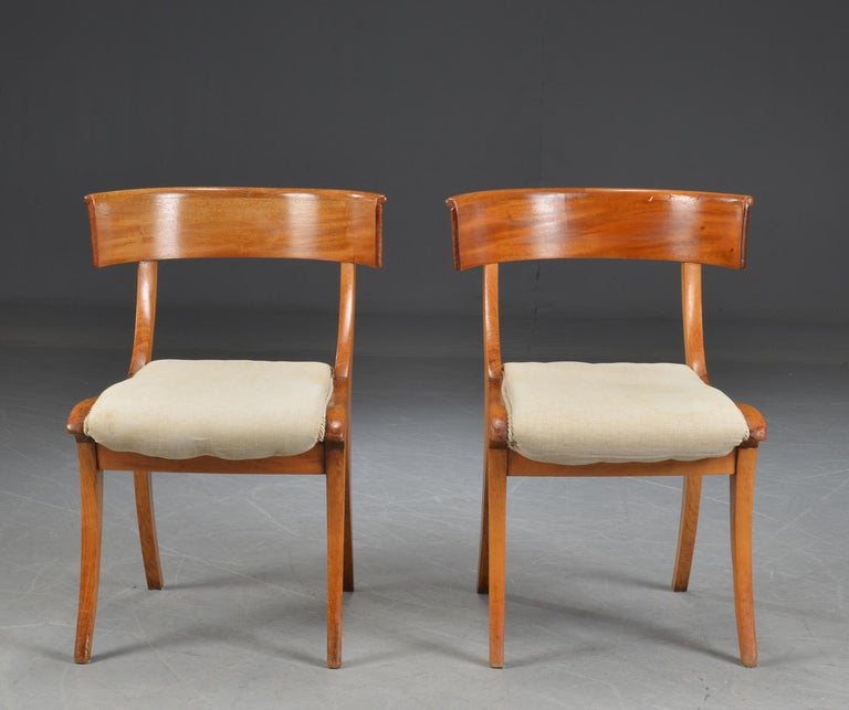 Pair Klismo chairs with curved mahogany lacquered frame. Seats upholstered in light beige upholstery fabric.