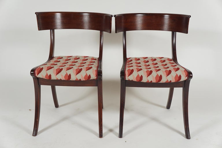 Pair of continental 'Klismos' chairs, in mahogany, late 19th century, with needle-point seats in a tulip design.