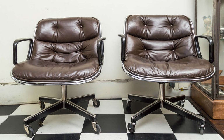 Pair of Knoll black leather Pollack Executive armchairs. Vinyl tub with seasoned leather button and tufted upholstery. Four legs on a stainless steel and metal base. Cast black resin arms. Designed by Charles Pollack for Knoll, 1963. In production