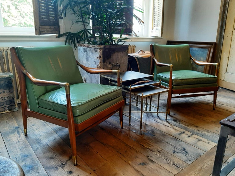 A pair of sculpted Danish modern 1960s brass accented lounge chairs; attributed to Ib Kofod-Larsen. These beautiful midcentury / vintage chairs, are each with incurved back and are upholstered in green leather which is studded on the back. The seats