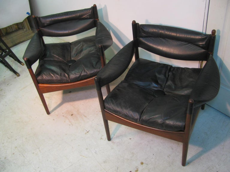 Beautiful pair of rosewood and black leather lounge chairs by Kristian Vedel. Leather sling arms with a drop in leather cushion. Elegant rosewood frames with arched curves and turned leg posts.