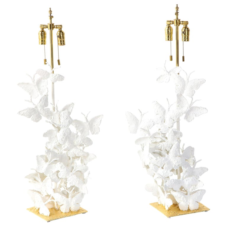 Decorative pair of butterfly lamps. Made of metal, covered with white plaster and the bases are covered with gold leaf. The butterflies reach 27 inches. Total height with lamp shades measure 33.75 inches. Designed and produced by a local artist in