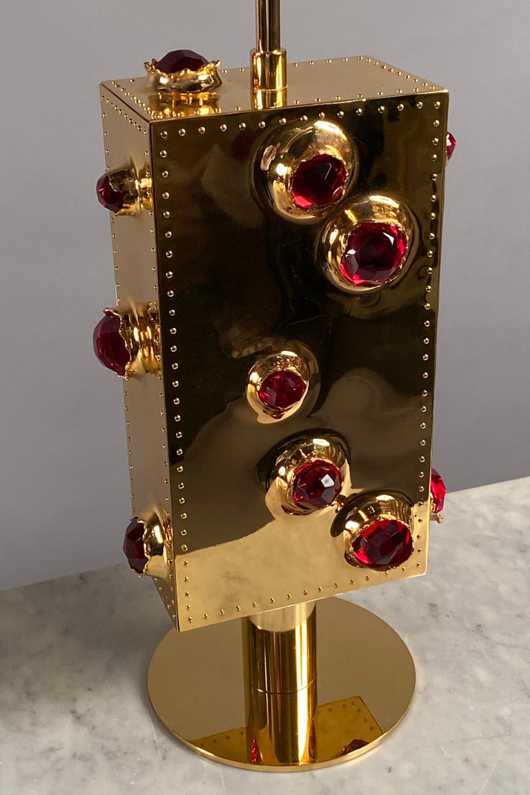 Pair of table lamps, each comprising a rectangular body clad in riveted gilded bronze plates featuring faceted ruby red glass encrustations.