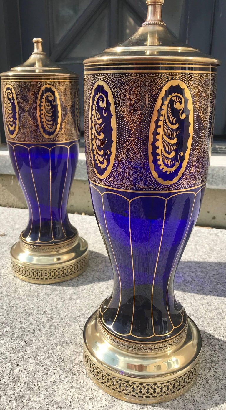 This elegant pair of handblown cobalt blue glass vases were converted into lamps in the 1930s. The gold patterns are hand applied in 24-karat gold. The lamps with tops measure 29