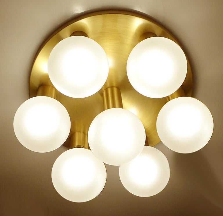 Pair of large midcentury flush mount Lights / sconces with seven lights , burnished brass base Measures: 10.62 in. / 27 cm H (with bulbs) Diameter 16.53 in. (42 cm). Seven bulbs with max 60 watts each, best used with large globe bulbs as shown
