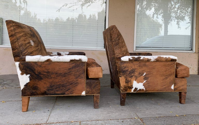 """Pair of large armchairs upholstered in brown cow hide with nailhead trimming. The chairs are in excellent condition, vintage but newly upholstered. Measurements: 37"""" high x 32"""" wide x 39"""" deep x 20"""" seat height x 25"""" seat depth x 25"""" seat width x"""