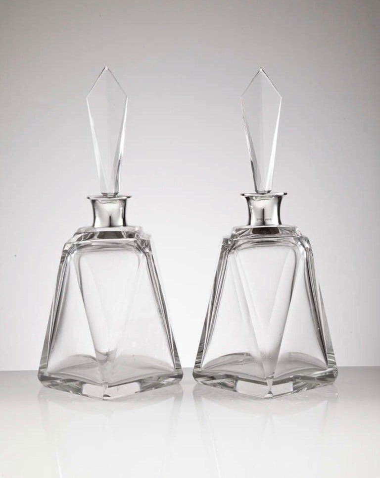 A pair of large Art Deco glass and English silver decanters fully dated London, 1920 by makers Hukin & Heath. The geometric form and elegant tall stoppers give them an overall stunning look.  We are always adding to our 1stdibs catalogue so be sure