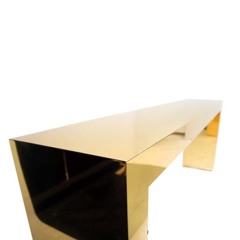 Large bespoke gold color brass metal console tables by Railis Kotlevs contemporary design Iceland used only in a movie set. These beautiful pair of consoles have an Art Deco shape and fleur. The very elegant forms and perfect proportions of the