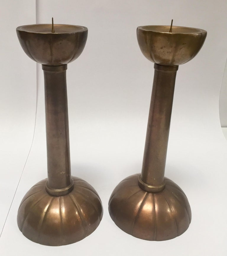 Fabulous pair of large brass candlesticks on a round scalloped base. Tall form with scalloped base and upper part underneath of the candle prong. They are a true beauty and will fit any environment. Cast iron brass, rose color, nice patina.