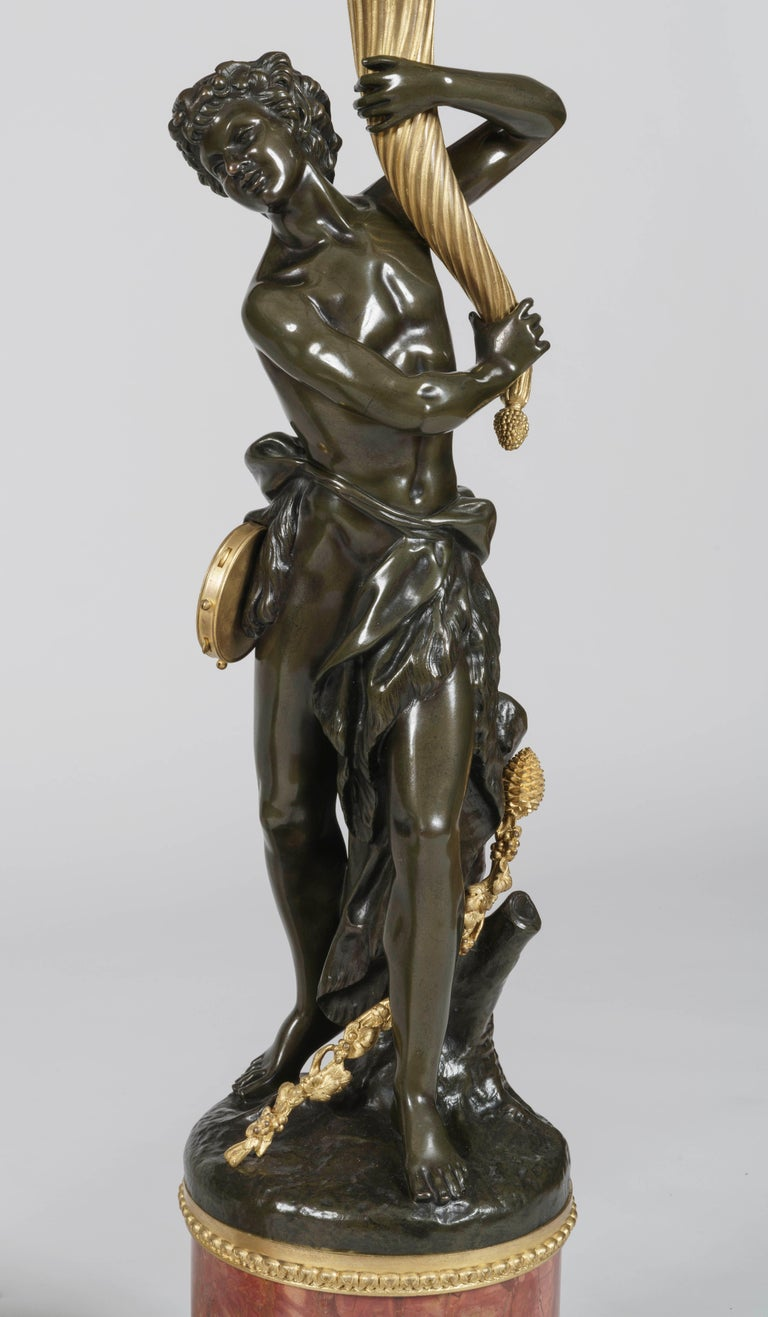 A substantial pair of gilt and patinated bronze candelabra After the model by Clodion (1738-1814).  Rising from important circular Rouge de Vérone marble bases, the gilt- and patinated-bronze figures of female and male Bacchic figures after the