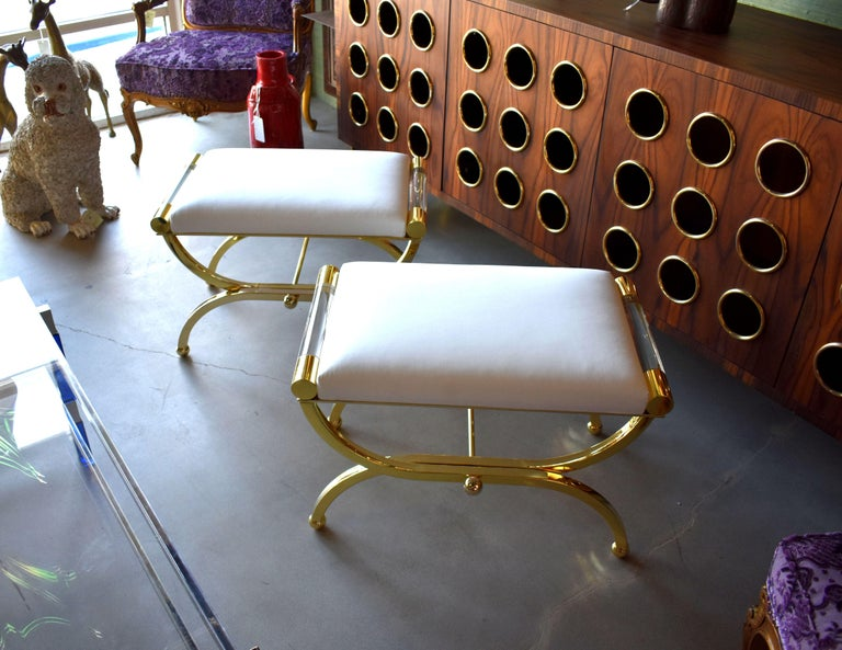 A pair of Regency benches design and signed by Charles Hollis Jones. Each bench is made of brass and Lucite with a faux white leather cushion.  Provenance directly from CHJ.  About Charles Hollis Jones:  Charles Hollis Jones is an American artist