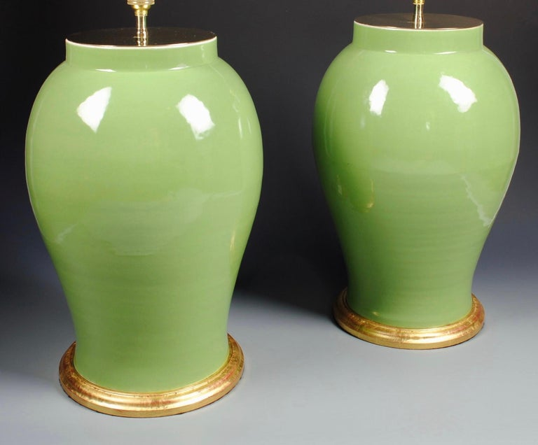 A fine pair of large Chinese green glazed vases, now mounted as table lamps, with hand-gilded turned bases.