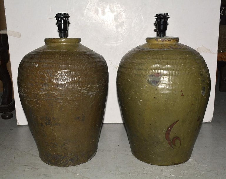 The large rustic vintage Chinese water or wine storage jars made into lamps. En relief bands circle the top of the jars, with wonderful organic color, form, and balance. Lamps are not an exact match as these are all individually made and unique.