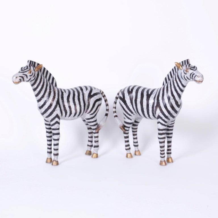 Rare and impressive pair of large cloisonné or enamel on brass zebras with their familiar iconic stripes, exposed brass ears, eyes, lips and hooves over a paisley field.