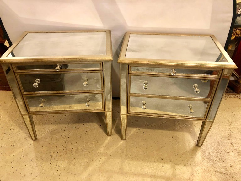 Pair of Hollywood Regency style custom three-drawer antiqued mirror nightstands or commodes. Mirrored on all sides including the back on these fine custom quality mirrored commodes or night stands. Each having two drawers under a pull-out serving or