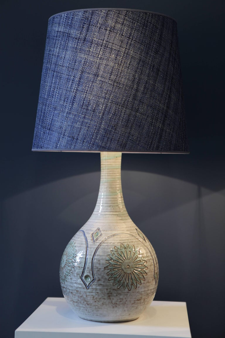 A pair of large and beautiful stoneware table-lamps Signed to the underside 'Bornholms Stentøj Søholm Denmark' Midcentury relief design in soft blues and greens on a light pastel colored ground, glazed Special handmade denim blue raffia shades,