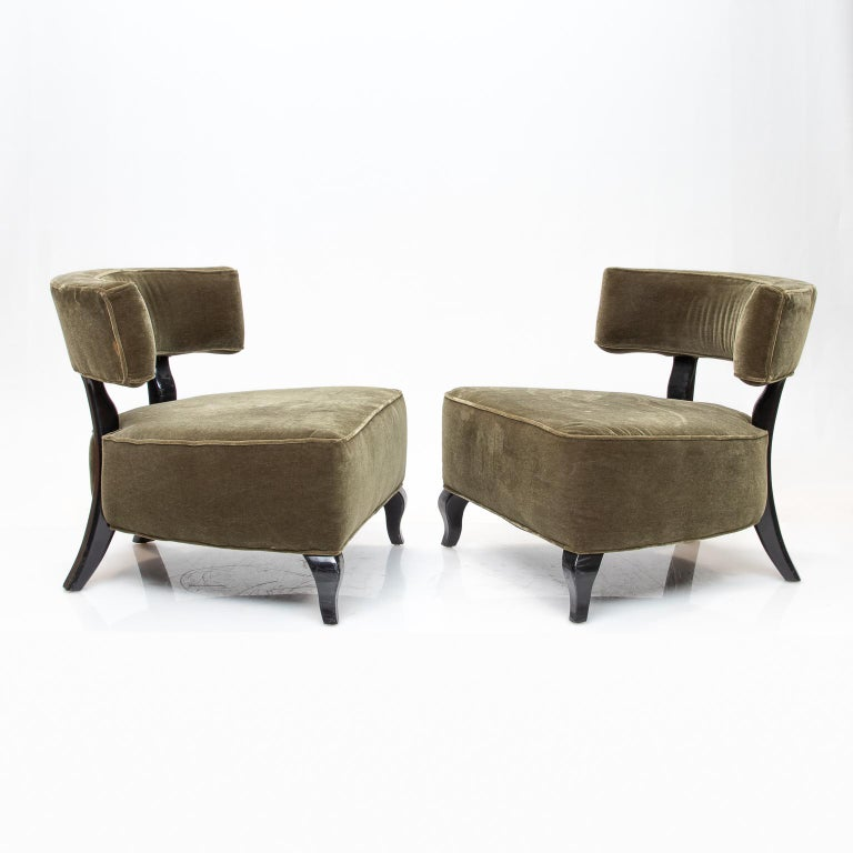 A pair of large Deco chairs in a light green mohair upholstery and black lacquered exposed wood. These chairs are very comfortable and big in appearance.