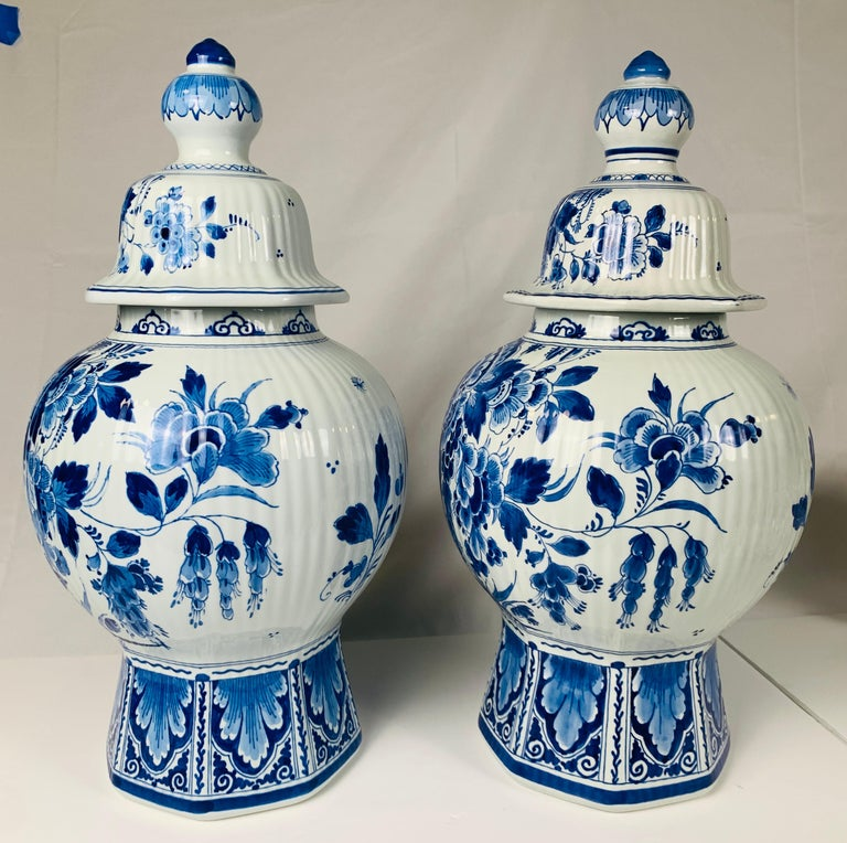 This pair of Dutch Delft blue and white jars are painted in a fabulous deep cobalt blue; showing a pair of quail under a wild profusion of flowers. The decoration is exquisite. The ribbed body rises from a traditional octagonal base, which is
