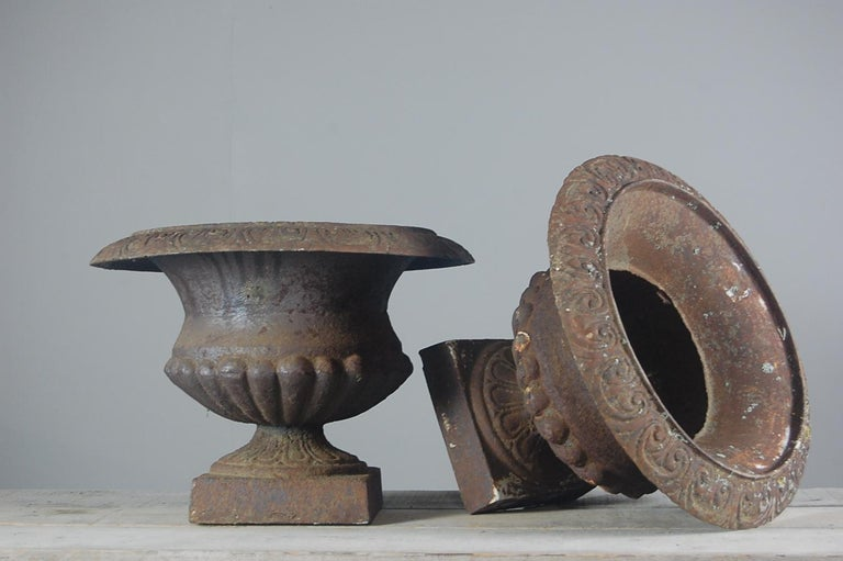 Pair of large, weathered early 20th century garden urns, in cast iron. France, circa 1920.