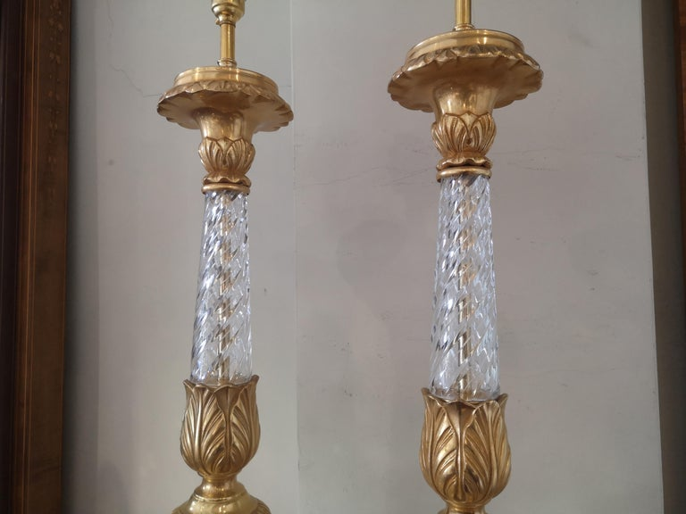 Pair of large early 20th century French crystal and gilded bronze lamps. The turned crystal stem with gilded bronze mounts and triform base with paw feet.