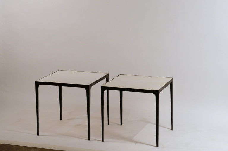 Pair of large 'Esquisse' wrought iron and parchment side tables by Design Frères. Also great as night stands.  Hand made, these elegant side tables combine chic slender blackened wrought iron bases with refined real parchment tops, adding an air
