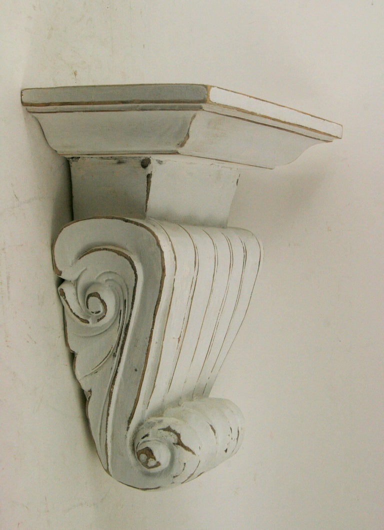 Pair of large hand carved wood wall shelves in a distressed white finish. Hanging hardware on back.