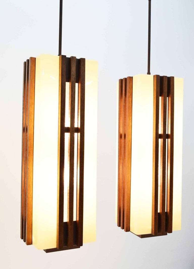 This is a gorgeous pair of large Frank Lloyd Wright style chandeliers or pendants. Lights are very well make and have a strong metal rod and frame that support plastic shades. Outside has rods of walnut on all four sides of each light. There are 6