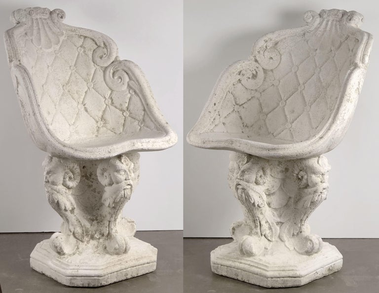 A fine pair of large French garden chairs of composition stone, each chair featuring a back and seat with a shell and scroll design, over a pedestal base with four Gothic figural heads.  Dimensions are H 34 3/4 inches x W 20 1/2 inches x D 22 1/2