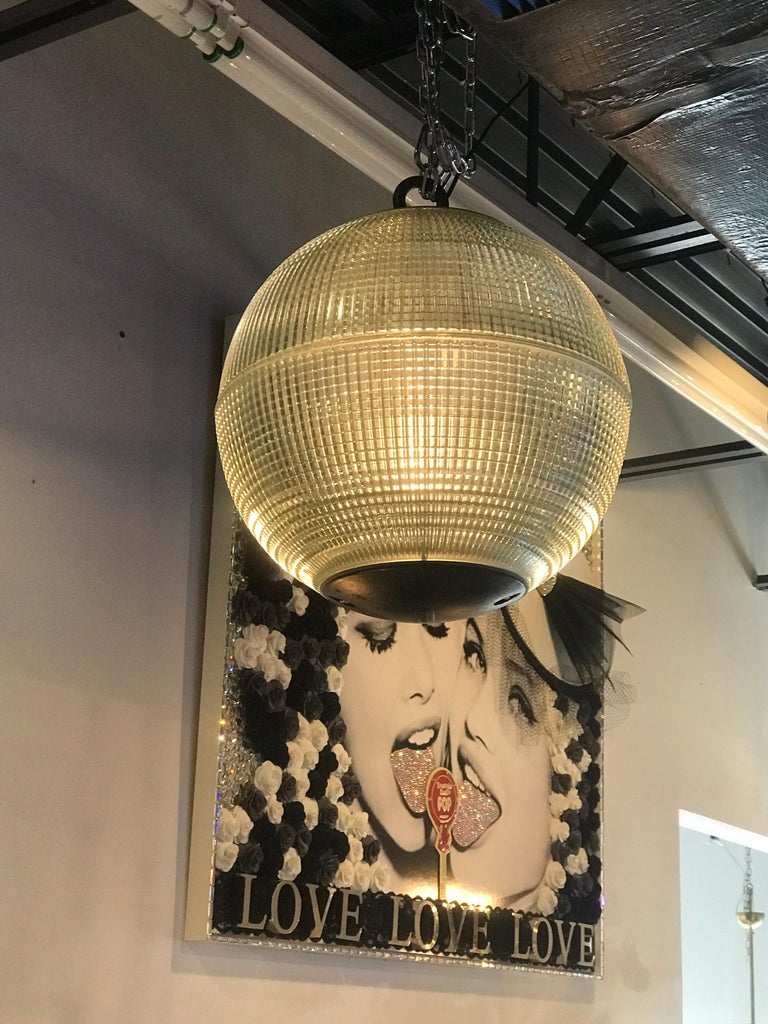 A wonderful very large spherical globe, originally a Paris streetlight and transformed into a hanging pendant. The hallmark of Holophane luminaires, or lighting fixtures, is the borosilicate glass reflector/refractor. The glass prisms or ribs