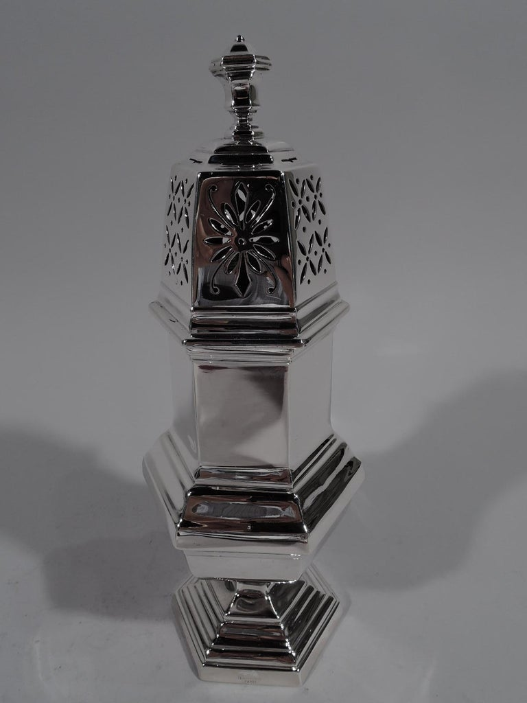 Pair of large modern Classical 950 silver sugar casters. Made by Tetard Frères in Paris, circa 1920. Each: Faceted hexagonal form with baluster body and stepped foot. Threaded domed cover with vase finial. Sides have stylized floral piercing in