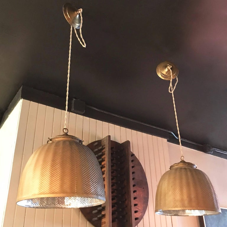Pair of large, industrial pendant lights feature X-Ray mercury glass shades with painted gold exteriors and reflective silver interiors with brass fitters and canopies. The lamps are newly wired with 36 inches of braided beige cloth cord to accept