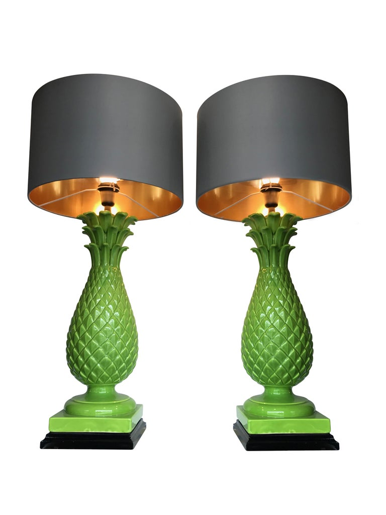 A pair of large Italian ceramic green pineapple lamps with black bases. Rewired with new chrome and black fittings, black antique cord flex and new switches. With new bespoke slate colored shades with gold linings.