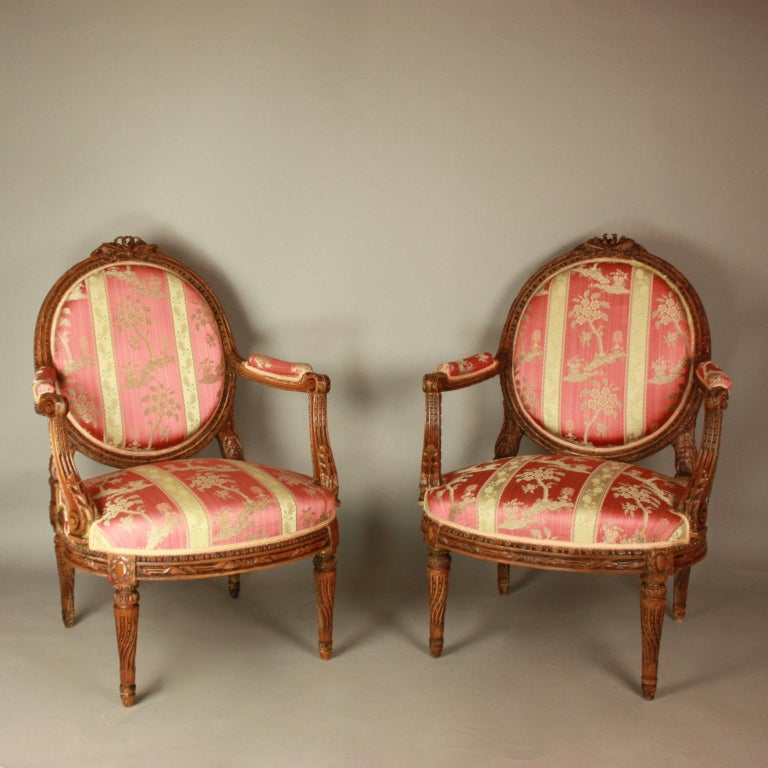 A pair of Louis XVI style walnut fauteuils of generous proportions. Each with a medallion back, padded arms and seat, the top rail centred by ribbon tied foliate featuring respectively a flute and arrows, the fluted frame with finely carved winding