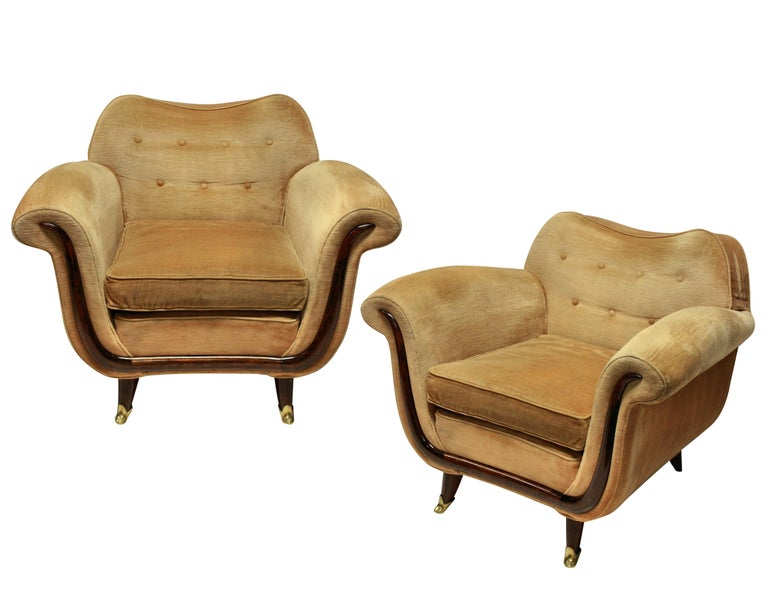 A pair of large and comfortable lounge chairs by Guglielmo Ulrich. With sculptural mahogany detailing and feet with brass sabot. In their original cleaned velvet, which is in good order, but can be upholstered to any specification.