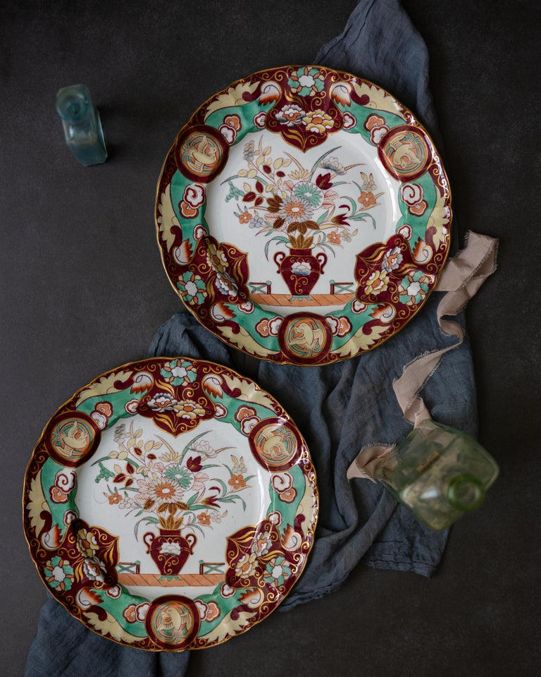 A pair of Mason's ironstone dishes decorated in the Regency chinoiserie style, circa 1860. The plates' pattern, Fence Vase Doves, is rendered in maroon, mint green, and buff.  Mason's Patent Ironstone China was introduced in 1813 as a less