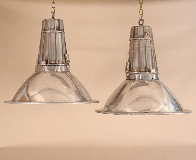 A very cool pair of aluminum industrial pendant lights, circa 1960. These midcentury floodlights have a clean, sleek form and an impactful size. They have been newly re-wired with porcelain sockets and the reflectors/lenses unclip to change a