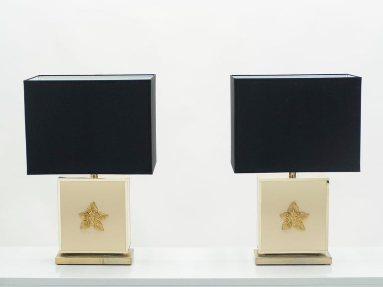 This pair of lamps is typical of designer JC Mahey's midcentury brass and lacquer work. A rich cream white lacquer base feels serious and sophisticated and is offset by brass accents, including a beautiful neoclassical sun head. Their minimal design