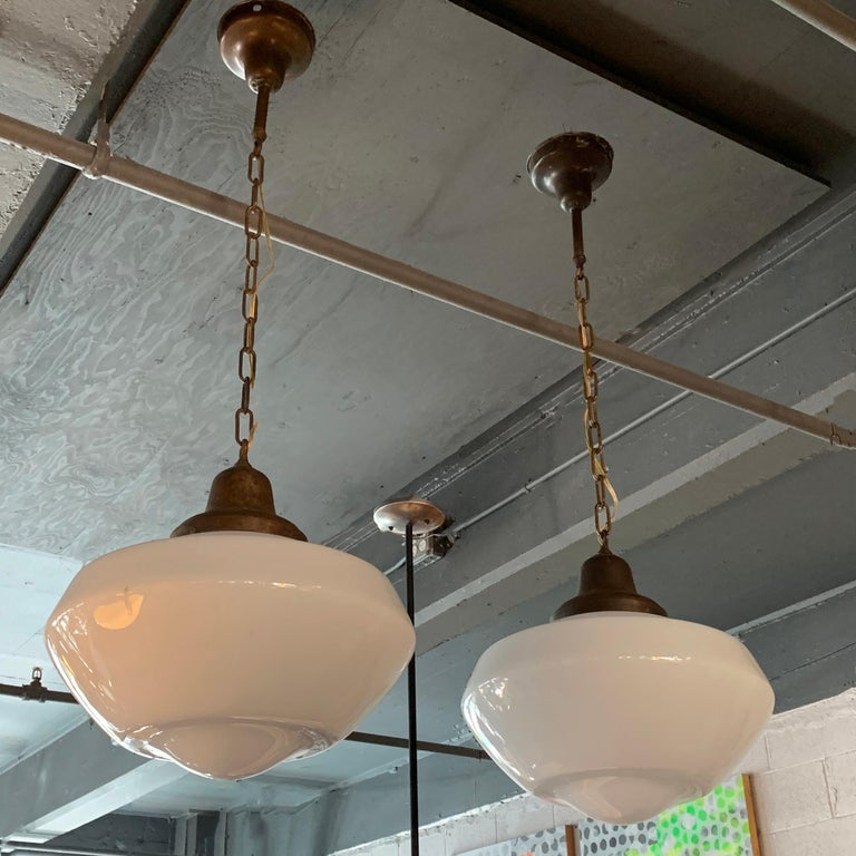 Pair of early 20th century, industrial, library pendant lights with molded, milk glass shades and brass fitters, chains and canopies are newly wired to accept a 200 watt bulb each. The overall height of the pendant is 26 inches; 17 inches of chain