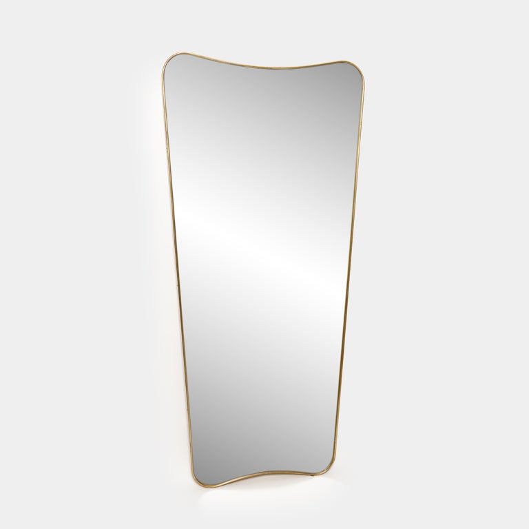 Pair of elegant and large patinated gilt brass framed mirrors with gently curved forms in the style of Gio Ponti. Solid construction with wood backing.   Sold individually or as a pair and price is for the pair.