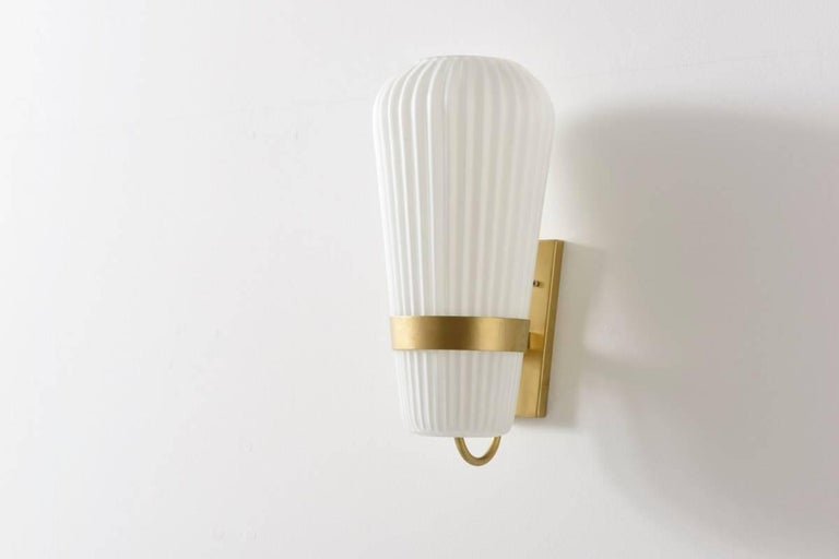 Pair of sconces very nice large sconces designed by L.Kalff for Philips, Holland, 1950s.  These fully opal ribbed glass lamps are hold by a metal frame gold painted and are in a very good condition, labeled by Philips. Shipping Complimentary.