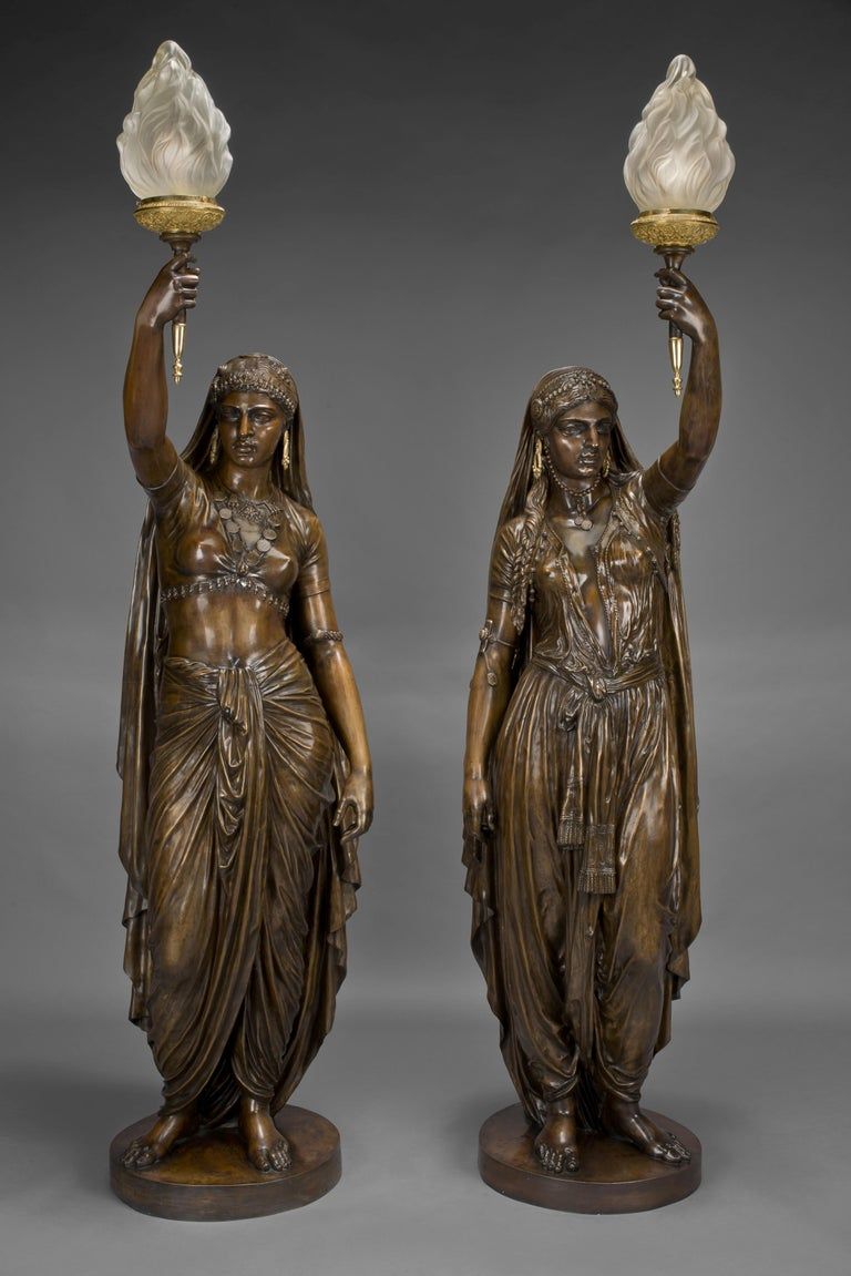 A highly important pair of large patinated bronze figural torcheres by Émile Guillemin, cast by Ferdinand Barbedienne.