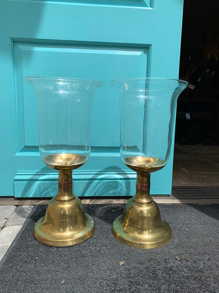 Pair of large scale Sarreid brass candlesticks with hurricane, circa 1980s Single copper-toned banding on brass candlesticks Glass hurricanes are clear. Turquoise shown is of our front door Measures: 10.5