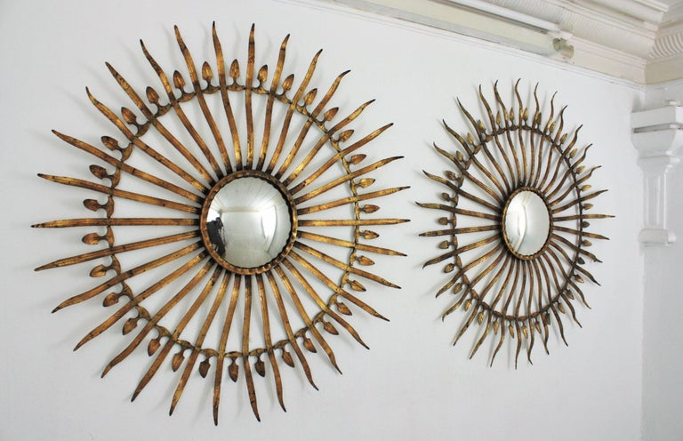 Pair of Spanish 1950s Hollywood Regency oversized gilt iron convex sunburst / starburst mirrors. Magnificent set of two large scale decorative sunburst mirrors. Handcrafted in iron and finished in gold leaf gilding. They have a terrific aged patina