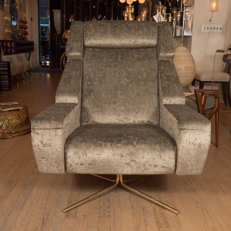 Pair of large scale upholstered swivel chairs with tubular base.