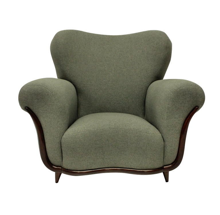 A pair of large Italian sculptural armchairs by Ulrich which is very comfortable. Newly upholstered in grey fabric and in a Minimalist fashion without piping or buttons, which accentuates the curved shapes. On tapering French polished feet and