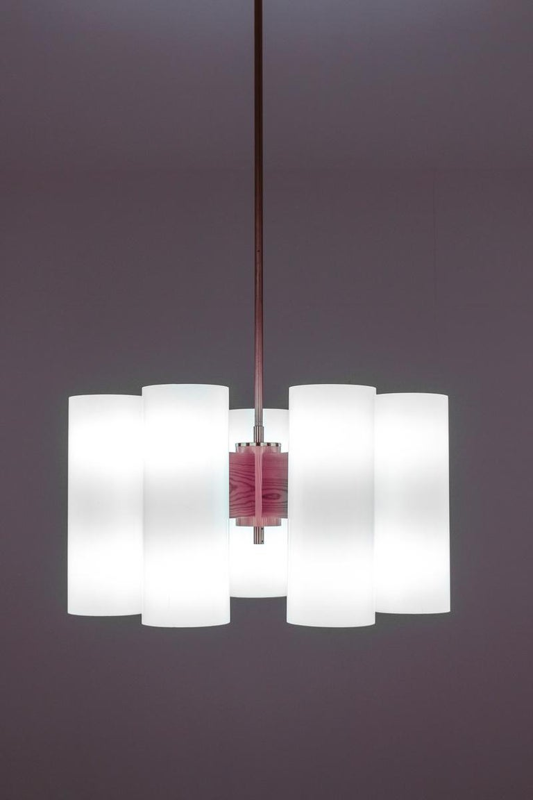 Rare chandeliers by Uno & Osten Kristiansson for Luxus. The chandeliers consist of six acrylic cylinders with two light sources in each cylinder. The cylinders are held by thick arms in pine that are fixture to the centrepiece. The lamps come with