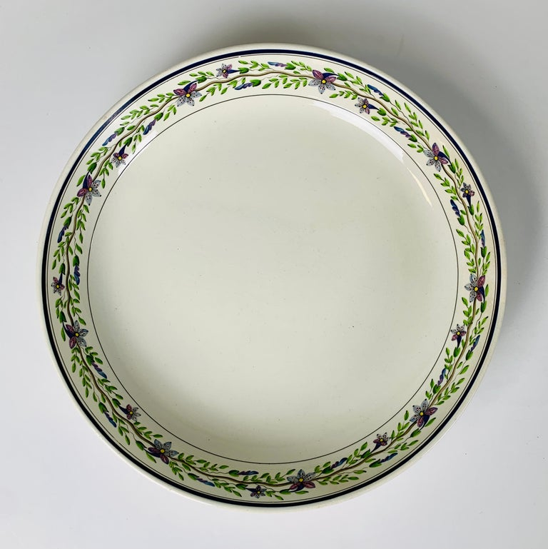 A pair of large Wedgwood bowls their borders painted with a lovely, delicate vine with lavender and lavender-pink flowers and green leaves. They are simple, understated, and beautiful. The underside of each bowl is marked with an impressed