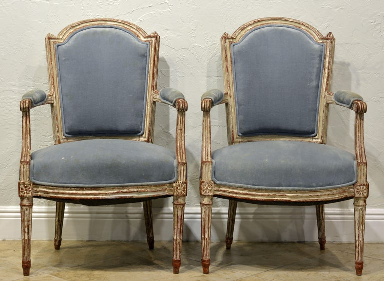 These very attractive French carved and painted armchairs dating to the Louis XVI period feature upholstered seats, armrests and backs in wonderfully detailed painted frames. The whitish paint shows decorative wear exposing underlying layers.
