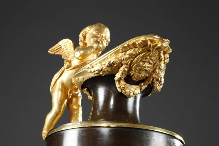 French directory pair of ewers in gilded and patinated bronze with handles in the shape of winged cupids. Both pitchers are decorated with ormolu garlands, a mask, and ribbons on the spout, while the paunch is encircled with a golden band. They rest